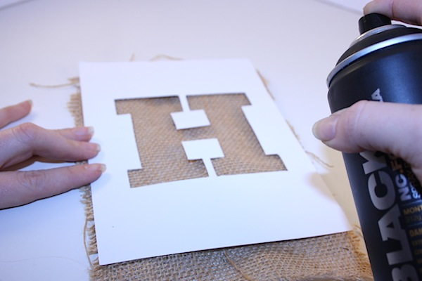 once you have your stencils ready take a piece of your bunting and centre the letter over it use your black spray paint to fill in the stencil